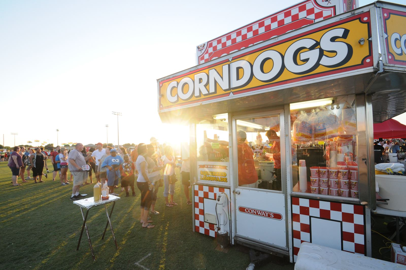 A line of people waiting to order food at a corn dog stand