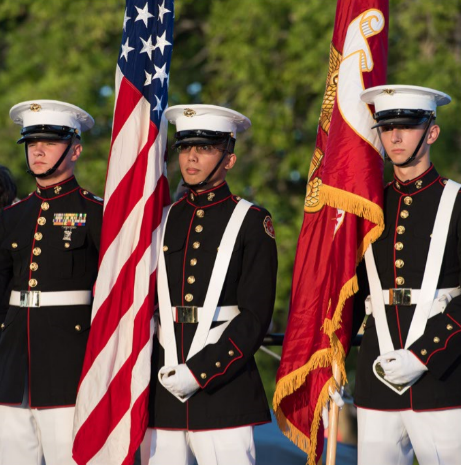 Three military men standing at attention holding flags