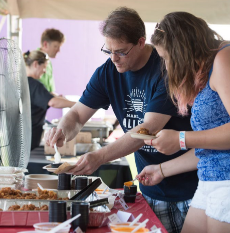 A man and a woman dishing up food at a buffet-style table at an outdoor festival