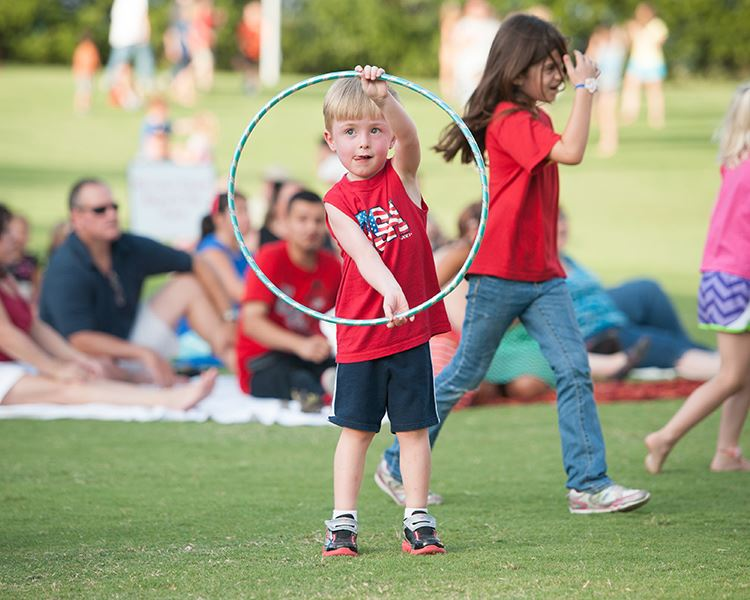 a young boy playing with a hula hoop