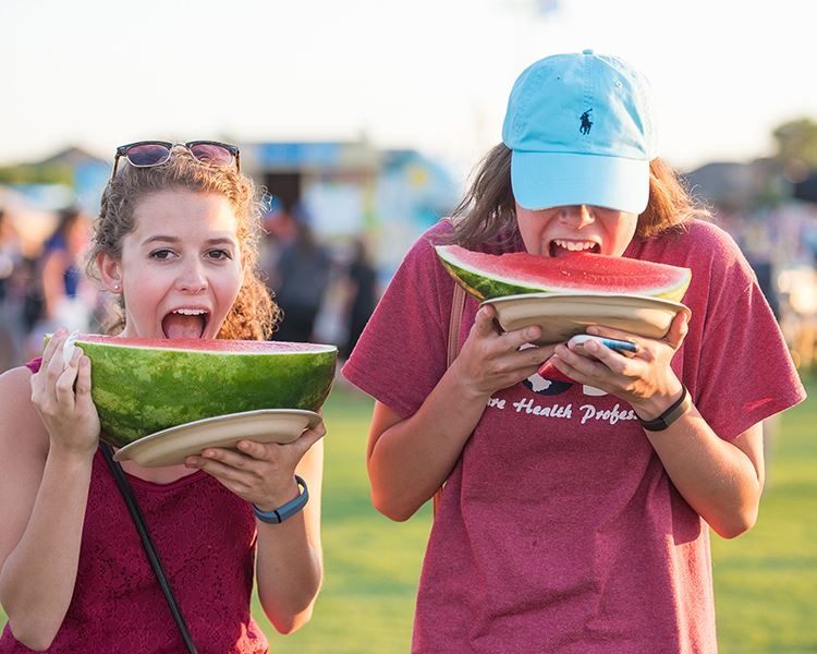 two girls eating huge pieces of watermelon