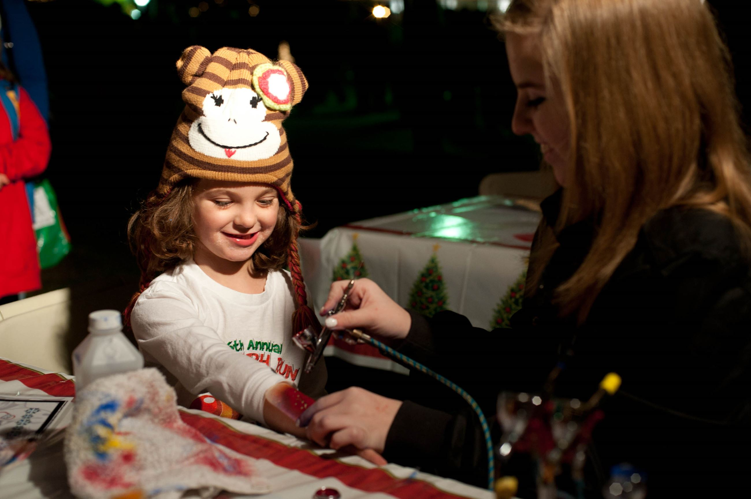 Young girl getting her face painted at the Holly Jolly Celebration